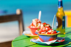 Bahamian conch salad. Two bowls of Bahamian conch salad and bottle of beer Stock Images