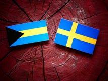 Bahamian flag with Swedish flag on a tree stump  Stock Image