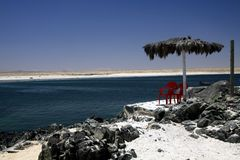 BAHIA INGLESA, CHILE - DECEMBER 26. 2011: White sand beach Playa blanca at pacific coast of Atacama desert with isolated red stock photography