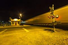 Bahnübergang mit dem Führen des Zugs bis zum Nacht lizenzfreies stockbild