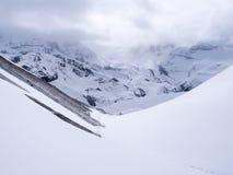 Bahn, die den nebelhaften Berg des Schnees mit bewölktem Wetterhimmel kreuzt Stockfoto