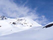 Bahn, die den Schneeberg mit bewölktem Wetterhimmel kreuzt Lizenzfreie Stockfotos