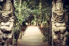 Bahn, die zu tropischen Wald mit schrecklichen Statuen von asiatischen Buddhismusdämonen auf beiden Seiten in der Weinleseart füh lizenzfreie stockbilder