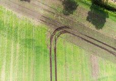 Bahn eines Traktors auf einem Feld, dem eine Wendung gemacht hat, wenn, die Feldgrenze, abstrakten Effekt erreichend durch vertik Stockbilder