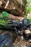 Bahn unter Felsen- und Wasserfällen stockfoto