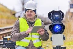 Bahnangestellter mit Tablet-PC nahe den Warnlichtern Stockfoto
