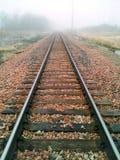 Bahngleisüberschrift in den Nebel stockfotos