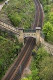 Bahngleise, die unter alte Ruinen überschreiten Lizenzfreies Stockbild