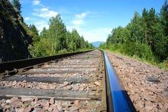 Bahnschienen und Lagerschwellen Die alte Eisenbahn durch den Wald Stockfotos