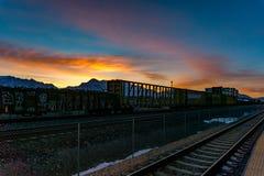 Bahnstrecken und Autos während eines erstaunlichen Sonnenaufgangs lizenzfreies stockbild