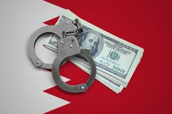 Bahrain flag with handcuffs and a bundle of dollars. Currency corruption in the country. Financial crimes royalty free stock photography