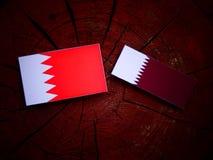 Bahrain flag with Qatari flag on a tree stump isolated Royalty Free Stock Photography