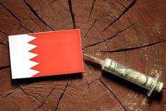 Bahrain flag on a stump with syringe injecting money stock photography