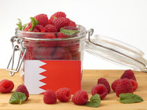 Bahrain flag on a wooden panel with raspberries isolated on a wh stock images