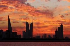Bahrain highrisebyggnader & imponerande föreställning fördunklar under solnedgång Royaltyfri Bild