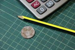 baht 5 de dinero tailandés en revés de una moneda con la calculadora y el lápiz en la placa verde del corte Imágenes de archivo libres de regalías