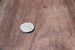 baht 5 en forma del nonagon del dinero tailandés antiguo en revés de una moneda con la forma de Garuda en el piso de madera foto de archivo libre de regalías