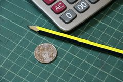 5 baht of Thai money in reverse of a coin with calculator and pencil on the green cutting plate. royalty free stock images