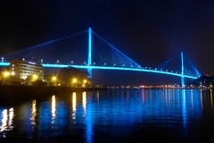 Bai chay bridge in halong bay Vietnam lit up with blue lighting reflecting off water Stock Image