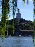 Bai Ta White Pagoda in Beihai Park, sunny day, boats and weeping willow in Beijing city, China. Relaxing time, touristic attraction, famous and renowned stock images