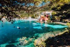 Baia adorabile dei assos villaggio, Kefalonia, Grecia Vista sull'acqua trasparente del tourquise incorniciata fra il boschetto ve fotografia stock libera da diritti