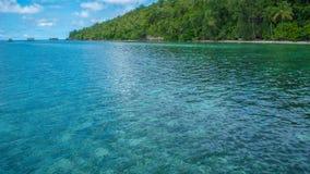 Baia davanti alla stazione di immersione subacquea ed all'alloggio presso famiglie sull'isola di Kri, alta marea, Raja Ampat, Ind Fotografie Stock Libere da Diritti