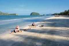 Donne tailandesi che selezionano i mitili alla spiaggia Immagini Stock