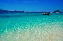 Baia del mare con acqua del turchese ed i pescherecci sotto il cielo luminoso Abbellisca il cielo blu ed il chiaro mare, il fondo Fotografia Stock