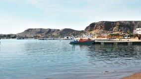 Baia del mare a stazione turistica tropicale parecchie barche, una spiaggia con i turisti e palme Bella acqua blu lento video d archivio