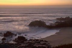 Baia della spiaggia con luce arancio del tramonto fotografie stock