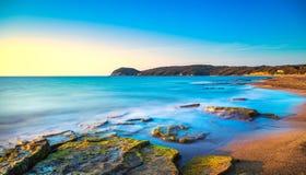 Baia della spiaggia di Baratti, collina del promontorio, rocce e mare sul tramonto Marem immagine stock