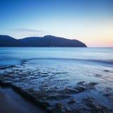 Baia di Baratti, collina del promontorio, rocce e mare sul tramonto La Toscana,  fotografie stock libere da diritti