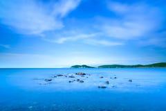 Baia di Baratti, piccole rocce in un oceano blu sul tramonto. La Toscana, Italia. Fotografia Stock