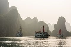 BAIA di HALONG, VIETNAM - ottobre 2014 - navi con i turisti nell'alone immagine stock