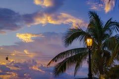 Baia di Nha Trang nel tramonto con il sistema della cabina di funivia e la lampada di via, rami del cocco su priorità alta Fotografie Stock
