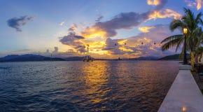 Baia di Nha Trang nel tramonto con il sistema della cabina di funivia e la lampada di via, rami del cocco su priorità alta Fotografia Stock Libera da Diritti