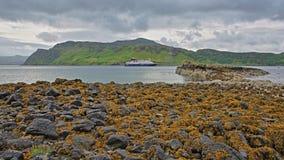 Baia di Portree con l'isolotto di Sgeir Mhor nella priorità alta ed in una spiaggia variopinta, isola di Skye, altopiani, Scozia, Fotografie Stock