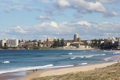 Baia idillica della spiaggia con la città Immagini Stock