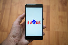 Baidu logo on smartphone screen. London, United Kingdom, june 5, 2017: Man holding smartphone with Baidu logo on the screen. Laminate wood background stock photos