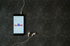 Baidu logo on smartphone screen. Los Angeles, USA, october 23, 2017: Baidu logo on smartphone screen and earphones plugged in on metal plate background royalty free stock photo