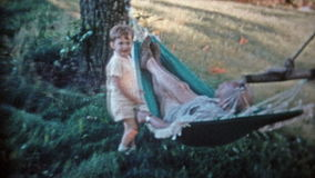 BAIE DE CHESAPEAKE, LE MARYLAND 1966 : Fils basculant le papa somnolent dans l'hamac extérieur d'été banque de vidéos