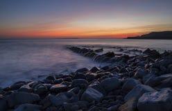 Baie de Kimmeridge avec les roches humides et le coucher du soleil image libre de droits