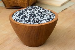 Baie de riz dans l'arc en bois sur la table photo stock