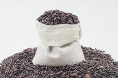 Baie de riz dans une poche en bois Images libres de droits