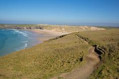 Baie du sud de Holywell de chemin de c?te ouest les Cornouailles du nord avec les vagues et le ciel bleus de mer photographie stock libre de droits