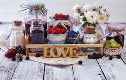 Baie fraîche et confiture faite maison dans des bouteilles décorées du tissu, du ruban et des fleurs Photo libre de droits