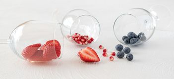 Baies dans verres à vin et baies sur une table de cuisine sur le blanc image libre de droits
