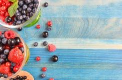 Baies de noir bleu et de rouge sur la nourriture saine de fond en bois bleu images libres de droits