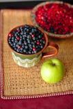 Baies et pomme sur la table Photo libre de droits