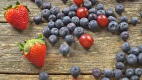 Baies fraîches sur la vidéo saine organique de hd de MOUVEMENT LENT de produits de fond de raisin de myrtilles en bois de fraise clips vidéos